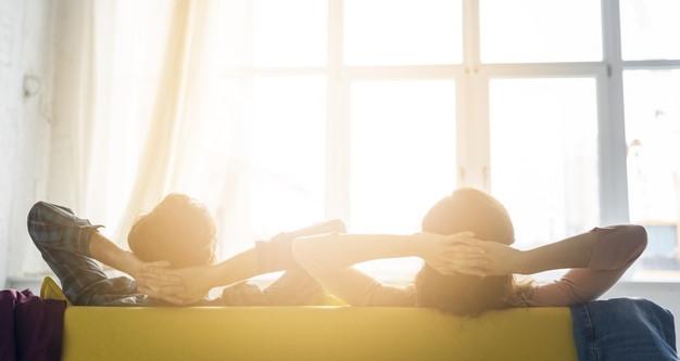 Ζευγάρι στον καναπέ κοιτάζουν παράθυρα