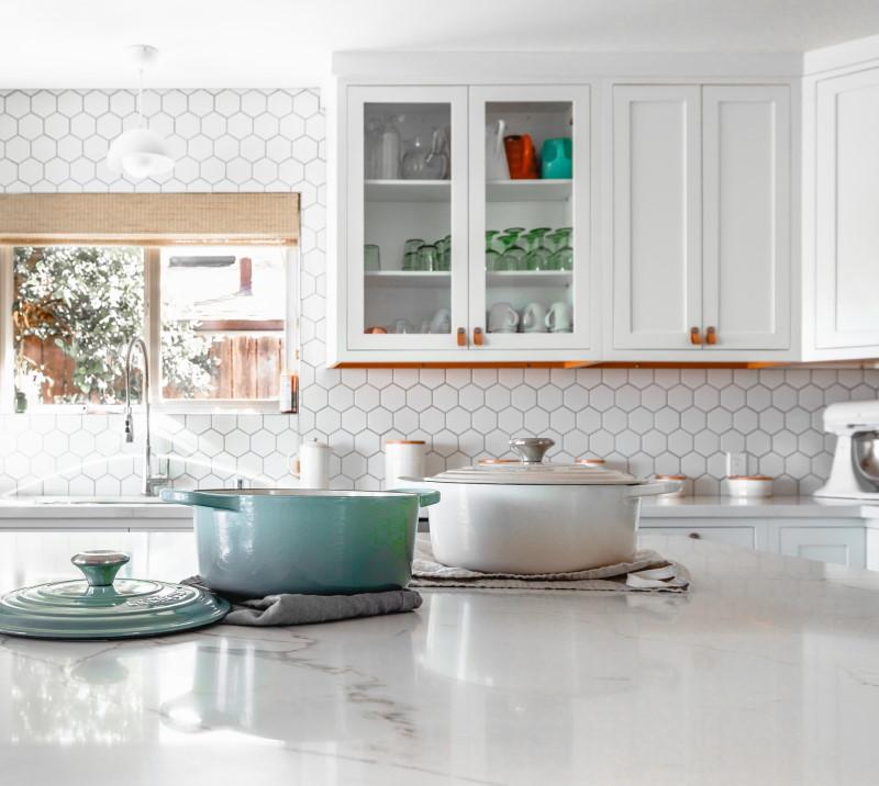 Λευκά ντουλάπια κουζίνας, κατσαρόλες και παράθυρο επάνω από νεροχύτη